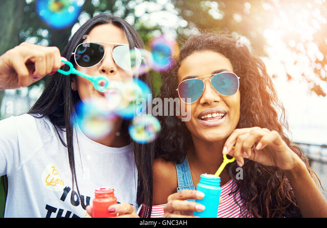 Diverse friends blow bubbles at the camera while wearing sunglasses under a setting sun - Stock Image