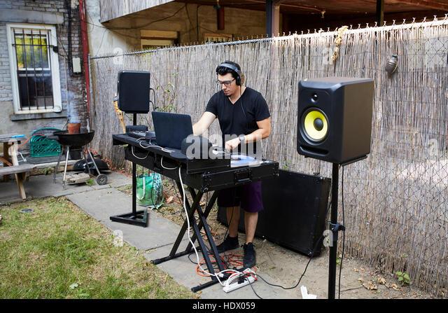 Hispanic dj playing music in backyard - Stock Image
