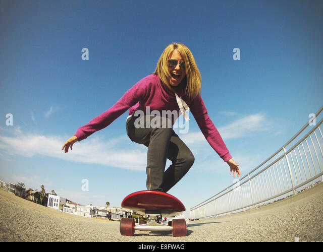 USA, California, Los Angeles, Venice Beach, Young woman skateboarding next to beach - Stock-Bilder