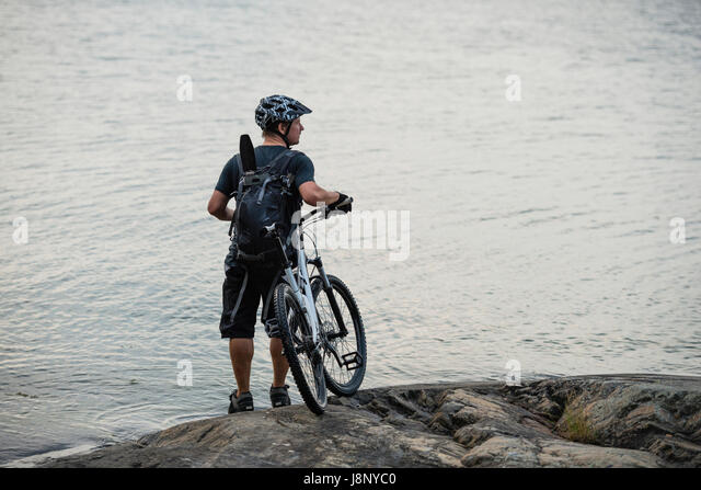 Man with bicycle standing by lake - Stock-Bilder