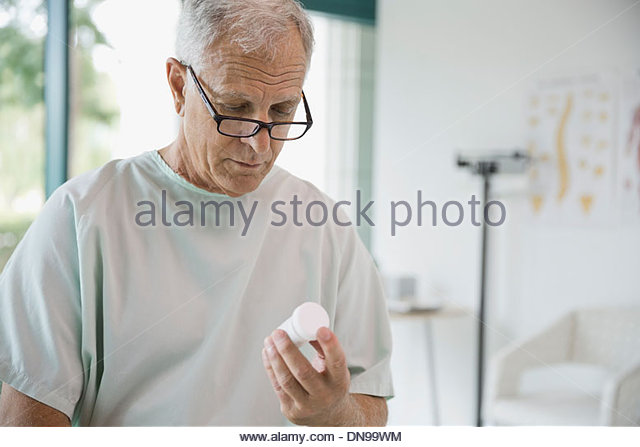 Senior patient looking at prescription medicine in hospital room - Stock Image
