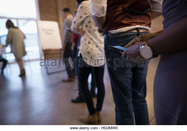 Business people waiting in registration queue texting with cell phone - Stock Image