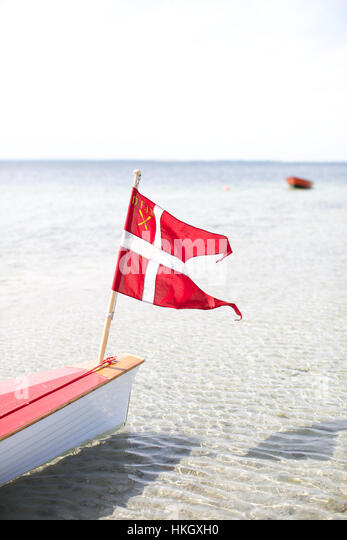 fluttering danish flag on boat. transportation, sea, environment, national flag. - Stock Image