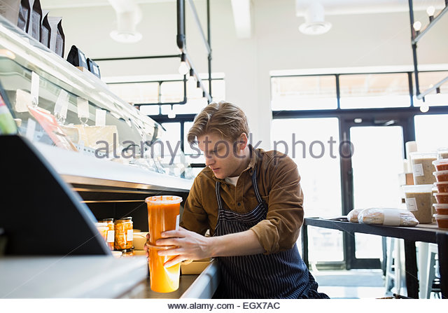 Market worker stocking soups in deli case - Stock Image
