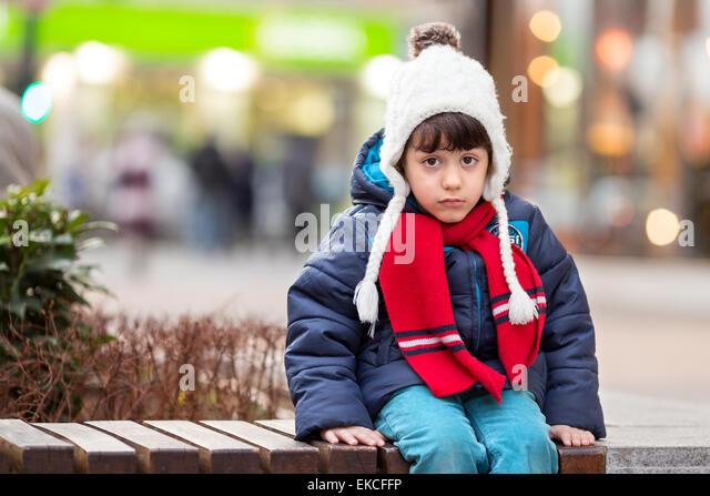 Sad boy sitting on a bench - Stock Image