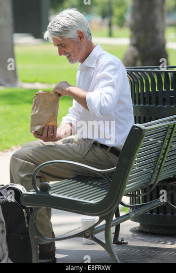 Businessman sitting on bench in park with his lunch - Stock Image