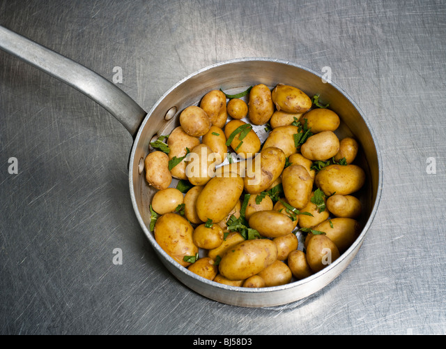 A steel pan containing new potatoes - Stock Image