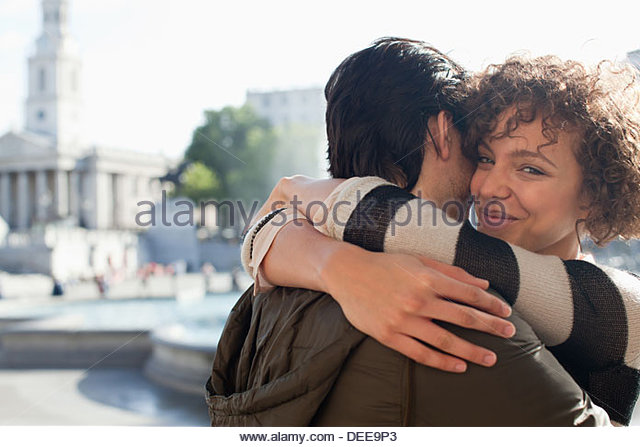 Happy couple hugging in city - Stock Image