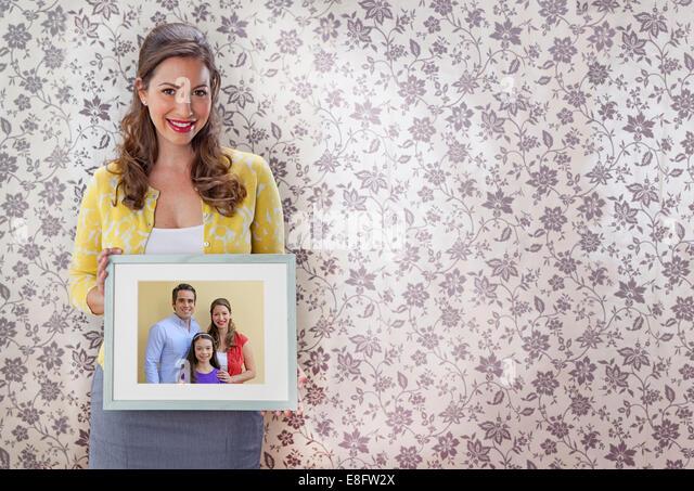 Woman holding family portrait - Stock-Bilder