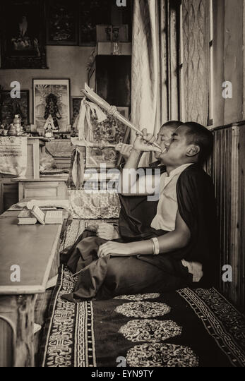 Buddhist priests, Lamas, praying inside a monastery in India, playing traditional flute with copy space in sepia - Stock Image