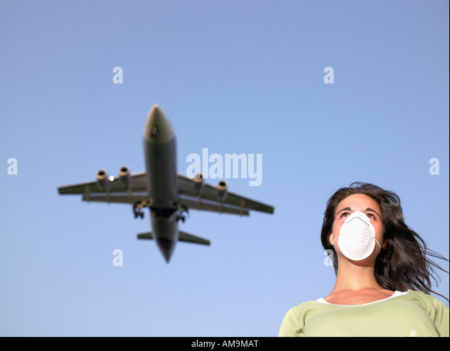 Woman wearing a surgical mask while a plane flies overhead. - Stock Image