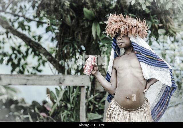 Tribal girl with a can of coke - Stock Image