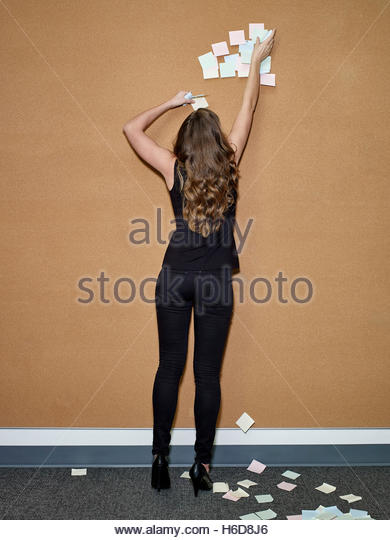woman reaching to remove sticky notes from wall - Stock Image