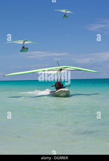 Motorised hang glider landing at sea, with boat, ultralight aircraft, UL trike, Varadero, Cuba, Caribbean, Central - Stock Image