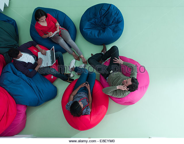 Men and women using laptop and cell phones in bean bag chairs - Stock-Bilder