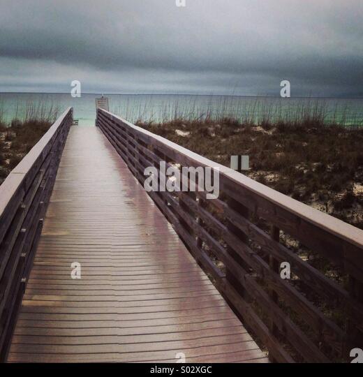 Wet beach walkway and stormy sky. - Stock Image