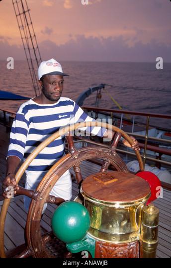 Venezuela Barefoot Windjammer SV Fantome steering helm Black man crew schooner cruise - Stock Image