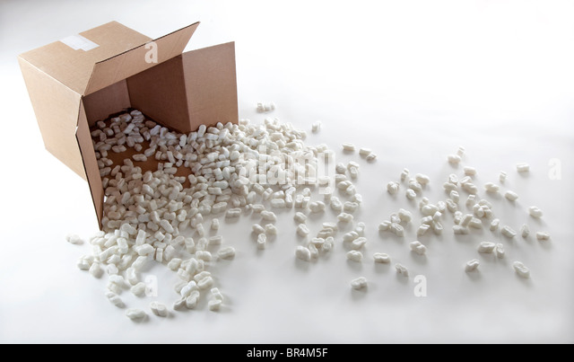packing peanuts spill from cardboard box - Stock Image