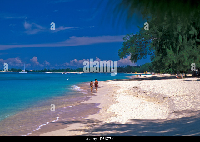Seven Mile Beach older mature couple walking beach Grand Cayman Island - Stock Image