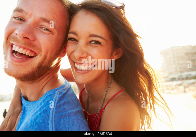 Young Couple Having Fun On Beach Holiday Together - Stock Image
