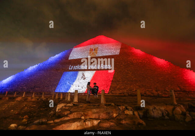 Cairo, Egypt. 15th Nov, 2015. Two Egyptians stay in front of the Great Pyramid of Giza being illuminated with the - Stock Image