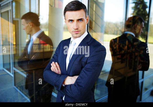 Portrait of a confident businessman standing with arms folded - Stock Image