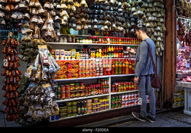 Young man selecting spices in market stall, Sao Paulo, Brazil - Stock Image