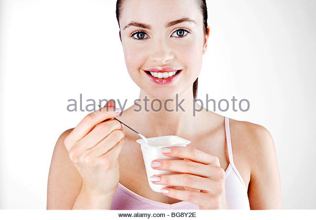 A Young Woman Eating A Yoghurt - Stock Image