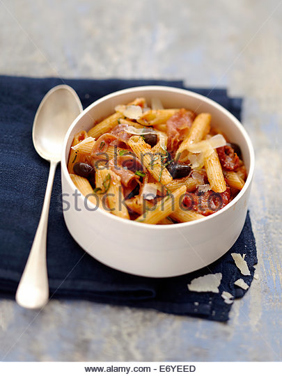 Penne with black olives,raw ham and sun-dried tomatoes - Stock Image