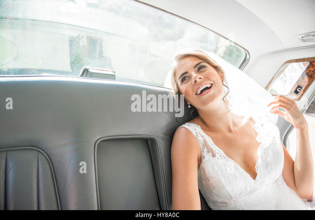 A bride sits in the wedding car after getting married - Stock Image