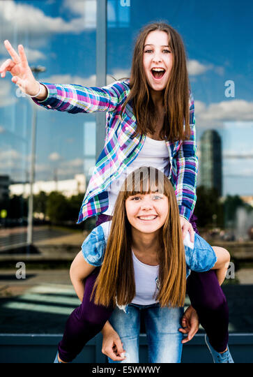 Two young women making peace signs and piggybacking - Stock-Bilder