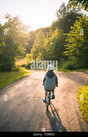Sweden, Bohuslan, Halleback, Boy (10-11) cycling away along asphalt road - Stock Image