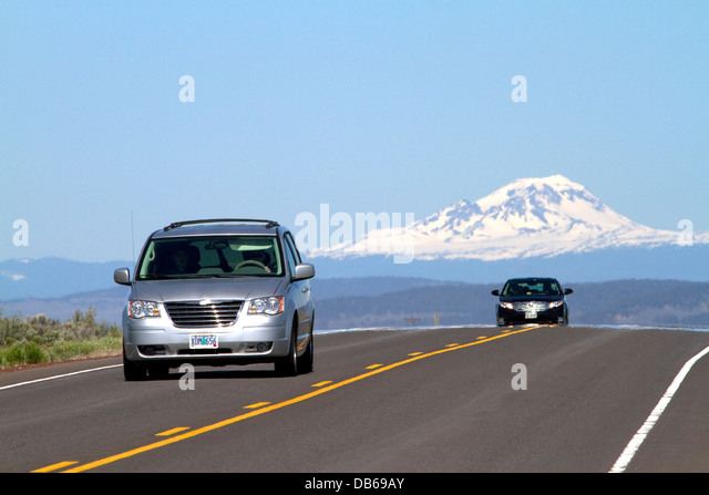 Automobiles travel on U.S. Route 20 east of Bend, Oregon, USA. - Stock Image