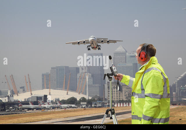 An environmental engineer monitors noise levels at London City Airport as plane takes off. Canary Wharf in background. - Stock Image