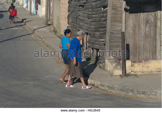 Elderly women crossing urban road on to sidewalk with a wooden house falling apart. Two people on bicycle in the - Stock-Bilder