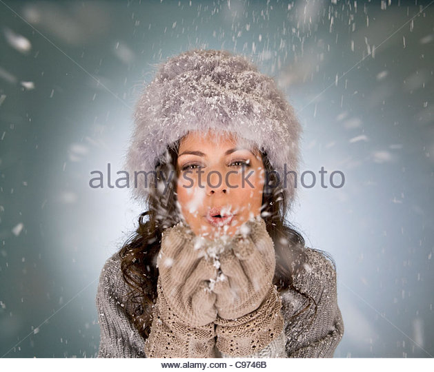 A young woman blowing snowflakes - Stock Image