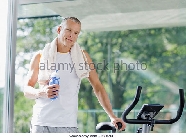 Man holding water bottle near stationary bicycle - Stock Image