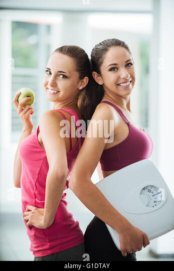 Happy teenage girl friends holding an apple and a scale, they are posing and smiling at camera, fitness and weight - Stock Image