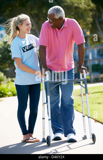 Teenage Volunteer Helping Senior Man With Walking Frame - Stock Image