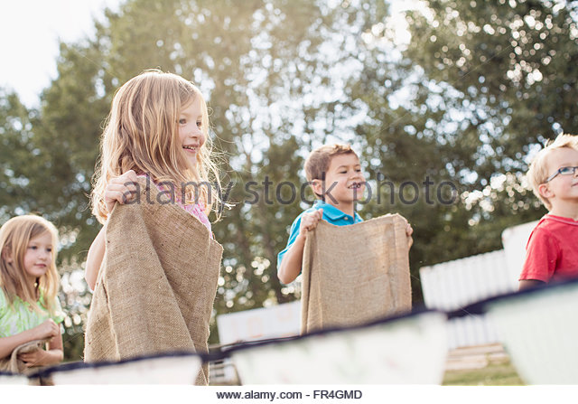 Cousins competing in a potato sack race. - Stock Image