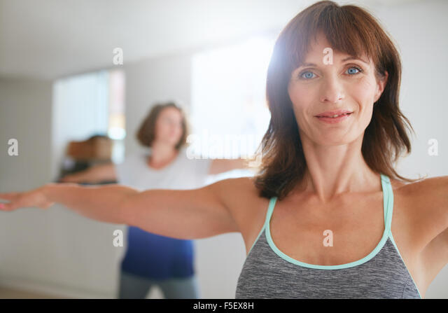 Two women doing stretching and yoga workout at gym. Female trainer with her student in background during physical - Stock Image