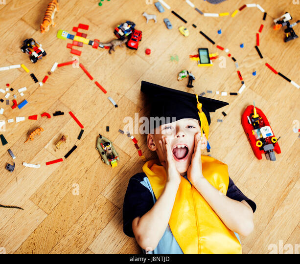 little cute preschooler boy among toys lego at home in graduate  - Stock Image