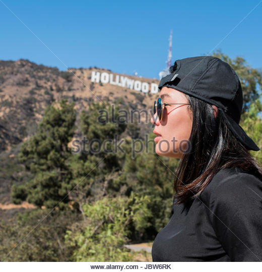Portrait of young woman in front of Hollywood sign, Los Angeles, California, USA - Stock-Bilder