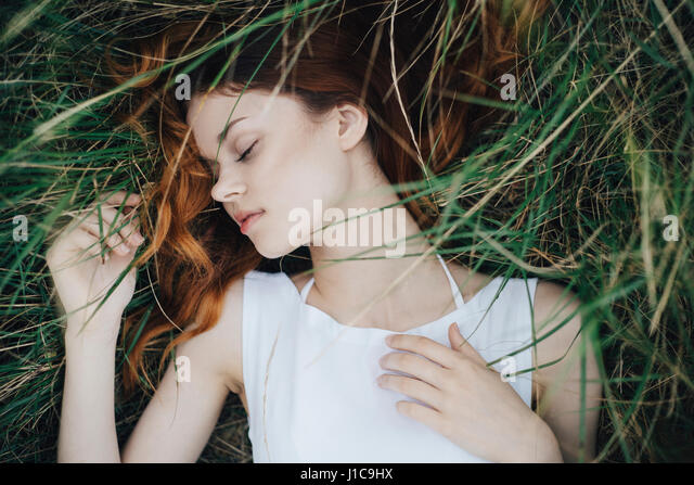 Caucasian woman napping in grass - Stock Image