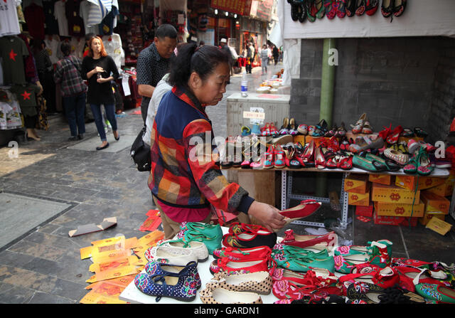 A Chinese woman is in an open market looking at cheap shoes she may buy. Qibao Old Street. Beijing, China. 26.04.2016 - Stock Image