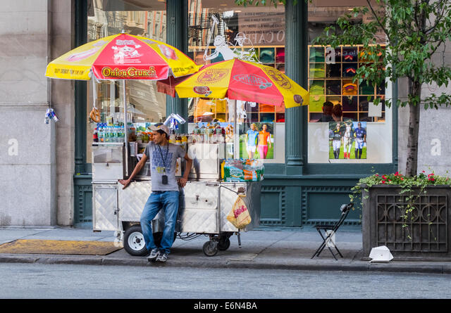 Young South Asian man selling soft drinks from a umbrella covered cart in Soho New York City Stock Photo