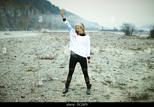 Woman standing in remote setting making peace sign - Stock-Bilder