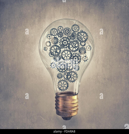 Light bulb concept with gears inside on cement background - Stock Image