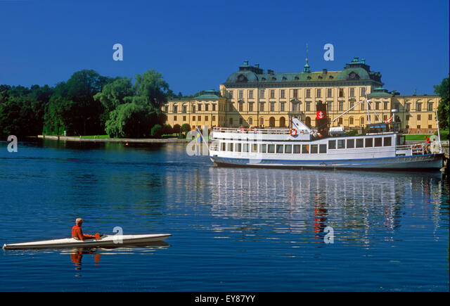 Ferryboat and kayak resting on calm water in front of the Royal residence at Drottningholm Palace near Stockholm - Stock Image