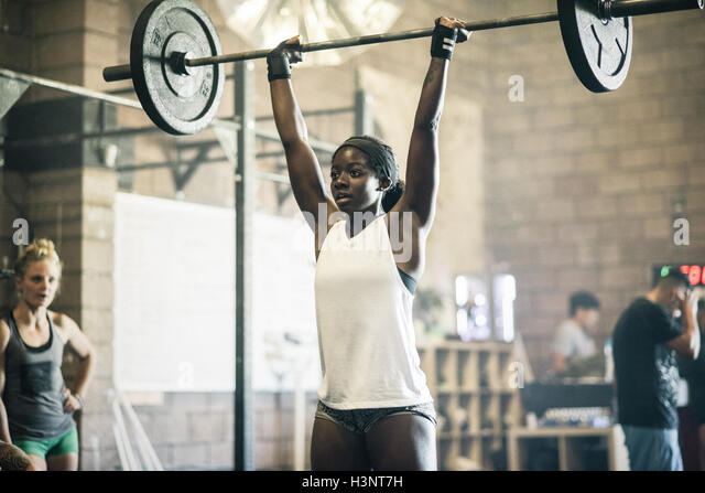 Cross training athlete lifting barbell in gym - Stock Image